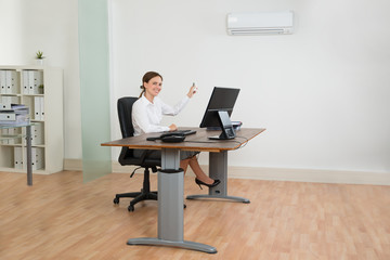 Businesswoman Using Air Conditioner In Office