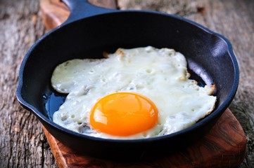 Aluminium Prints Egg Breakfast the fried egg in a iron frying pan