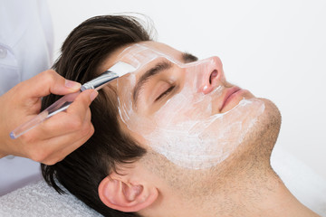 Therapist Applying Face Mask To Man