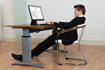 Businessman Leaning Back In His Chair While Working On Computer