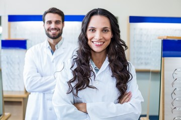 A female optician arm crossed with her colleague behind her