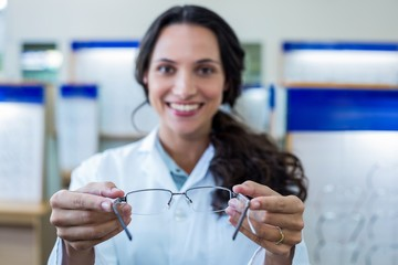 Blurry picture of a female optician showing glasses