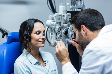 Optician using a phoropter on his patient