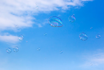 Soap bubbles flying in the air. Puffy clouds sky.