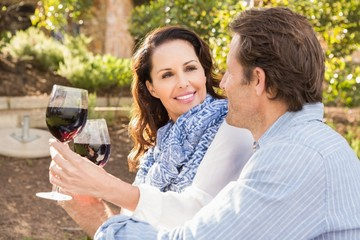 Cute couple smiling at each other while drinking wine