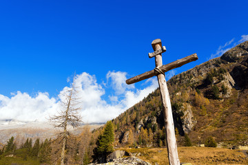 Wooden Cross - Italian Alps / Old wooden cross (trunks of trees) tied with ropes with blue sky and clouds in the National Park of Adamello Brenta. Trentino Alto Adige, Italy