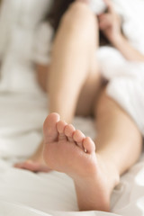 Two feet in a bed against a white background