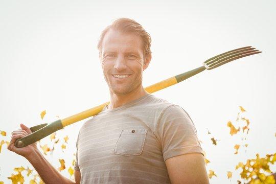 Happy handsome gardener plowing