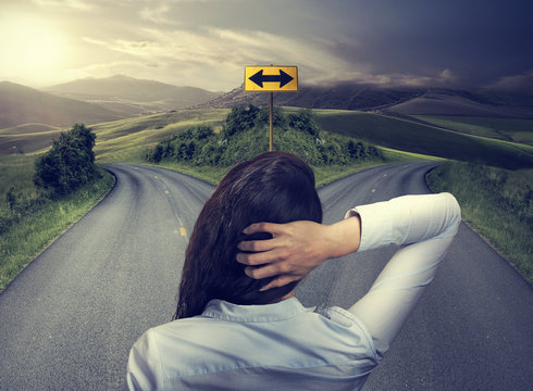 business woman in front of two roads thinking deciding