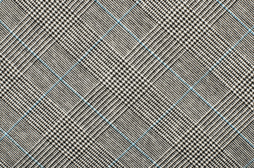 Black and white with blue houndstooth pattern in squares. Black and white wool twill pattern. Woven dogstooth check design as background.