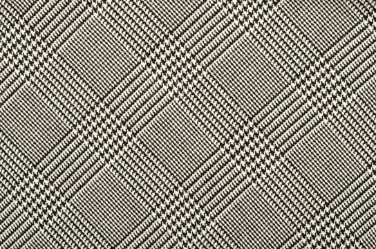 Black and white houndstooth pattern in squares. Black and white wool twill pattern. Woven dogstooth check design as background.