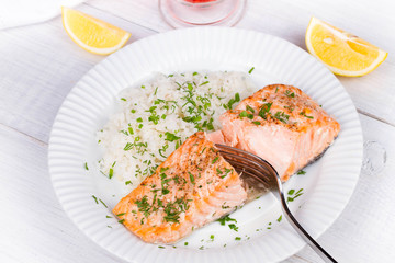 Steamed salmon with fresh herbs and lemon. Rice as a garnish