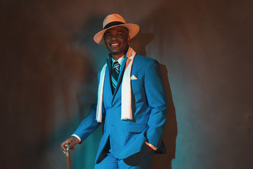 African american dandy man in blue suit and straw hat. Holding c