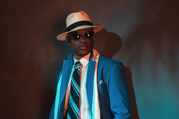 African american retro man in blue suit wearing straw hat and su