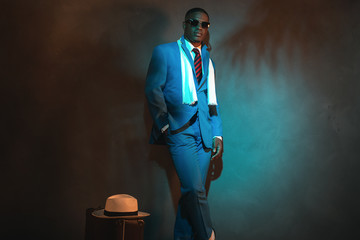 Retro african american traveller in blue suit and sunglasses. Wa