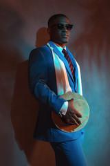 Retro african american man in blue suit wearing sunglasses. Lean