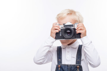 Pretty male child is making photos with joy