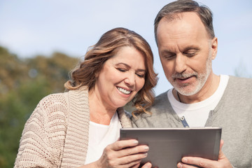 Cheerful old married couple is watching a tablet