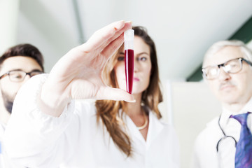 young doctors examines blood tube in laboratory