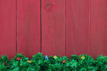 Green garland and gifts border rustic red wood background