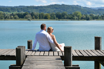 A couple on the wooden jetty at the lake. Switzerland