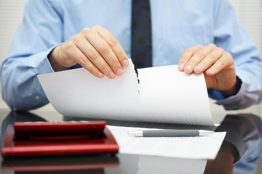 businessman tears document in office