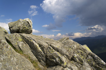 Boulder lying on a mountain peak with blue sky background