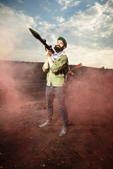 Man with AK-47 handgun and RPG bazooka posing as a soldier on dark field