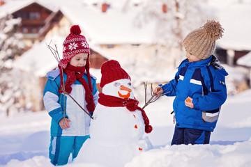 Happy beautiful children, brothers, building snowman in garden,
