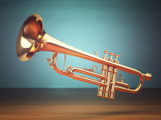 Polished brass trumpet on green background.
