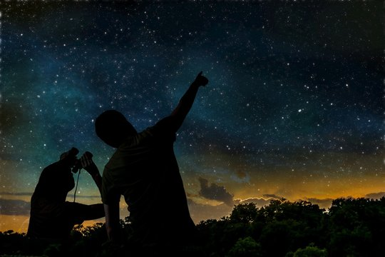 Silhouette of adult man observes night sky with child.
