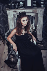 Gothic young woman in an elegant black dress in the armchair