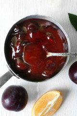 Tasty homemade plum jam in stew pot on wooden table, top view