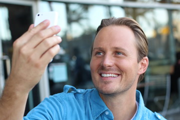 Young urban businessman professional on smartphone walking in street using app texting sms message on smartphone wearing a casual blue shirt