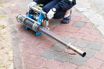 Worker preparing machine to fog with insecticides to kill aedes mosquitoes, carrier of dengue virus
