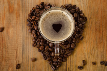 Glass cup of coffee on a wooden background.