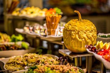 Salatbuffet mit kunstvoll geschnitztem Kürbis