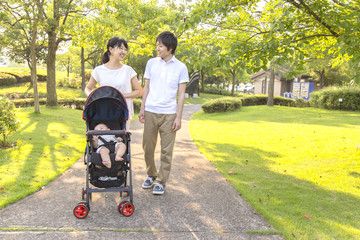 明るい公園でベビーカーを押す若い夫婦