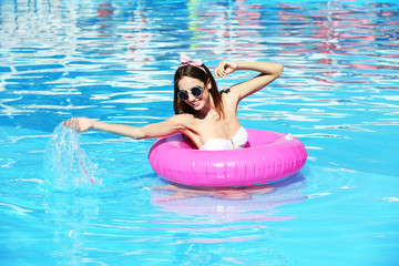 Young woman enjoying with rubber ring in swimming pool at summertime