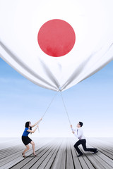 Japanese workers bring down a japanese flag
