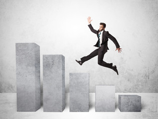 Successful business man jumping over charts on background