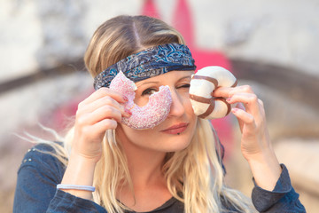 modern girl eating donuts on the street