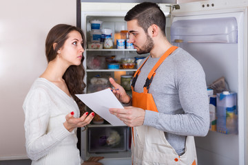 Repairman and housewife at kitchen