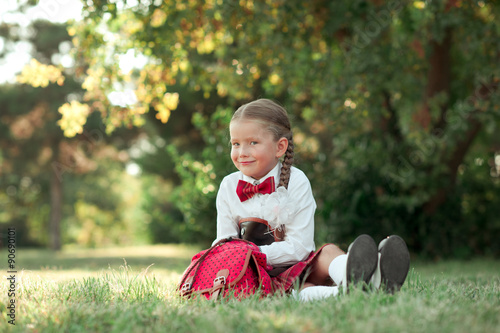 89164a54def Smiling baby girl 6-7 year old wearing school uniform outdoors. Holding  backpack. Looking at camera. School time. Back to school.