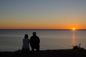 Couple at the coast by sunset