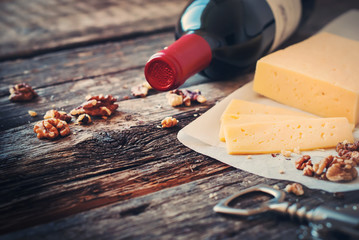 Red Wine, Wallnuts and Cheese on Wooden Table
