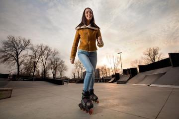 Smiling female inline skater rollerblading in a skate park