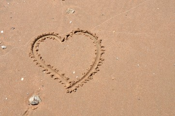 Heart carved into sand