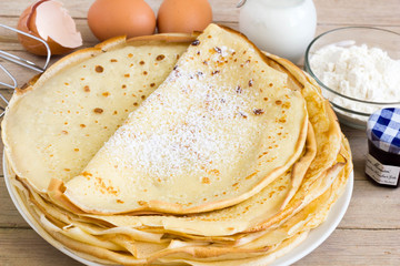 Crepes on each other with ingredients on the table.