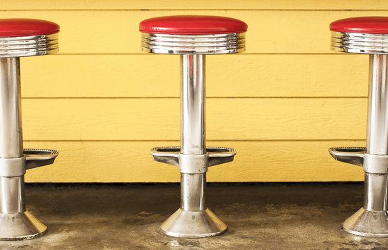 Three retro chrome diner stools.  Red vinyl seats, yellow background